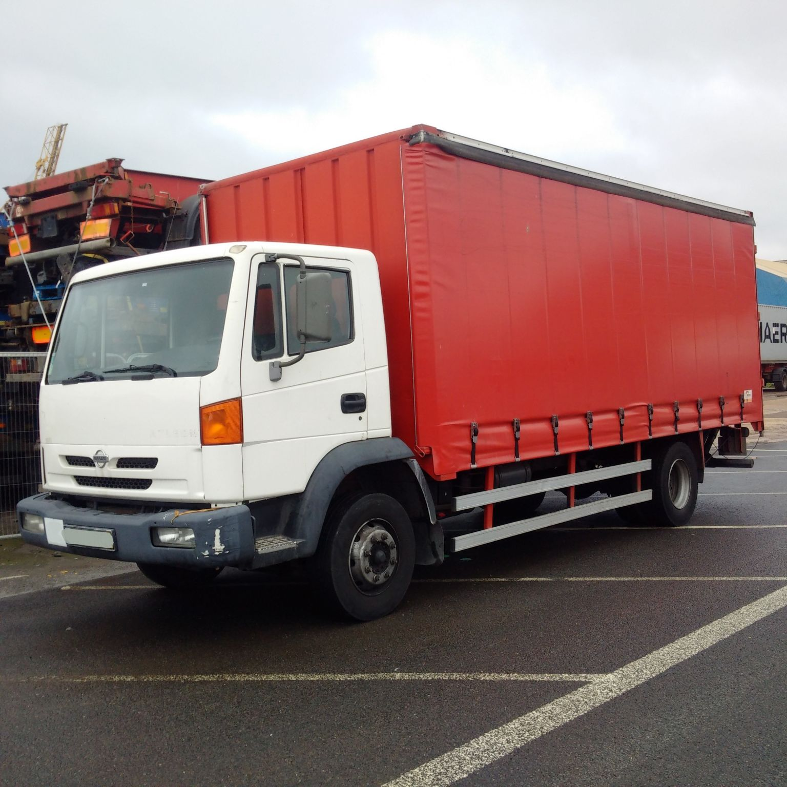 Left hand drive Nissan Atleon TK210 13 Ton curtainsider with tail lift.